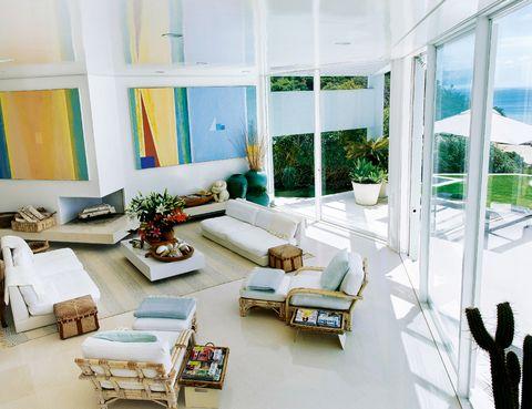 <p>El salón es un espacio luminoso, abierto al exterior y con una decoración dominada por el blanco. El punto de color lo ponen los grandes cuadros de Robert Jack.</p>