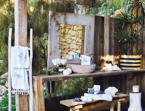 <p>Piedra, madera y fibras, trío ideal en este baño al exterior. Los complementos son de Zara Home</p>