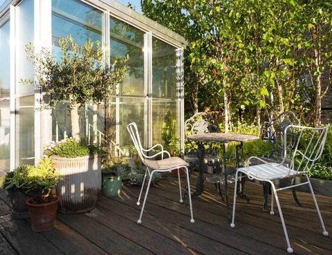 <p>En la planta de arriba se ubica la terraza, donde se ha creado un coqueto rincón con árboles y muebles de forja.</p>