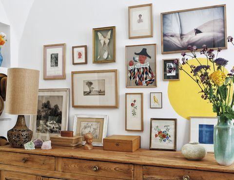 <p>Diversos cuadros y dibujos enmarcados con arte, como el paisaje del pintor <strong>André Dauchez,</strong> dan personalidad a este rincón del salón. Sobre el aparador de principios del s. XX, restaurado por los dueños, una lámpara de los años 70.</p>