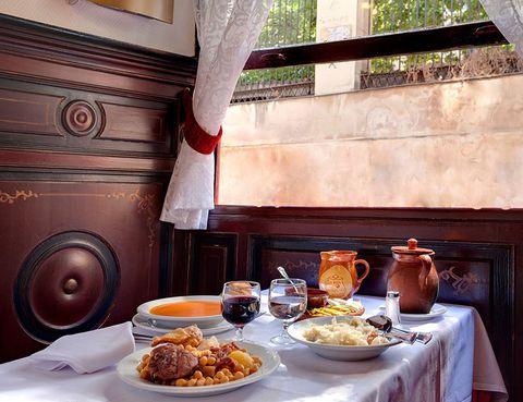 """<p>Si quieres disfrutar del tradicional guiso de la comunidad de Madrid sin duda tienes que visitar <a href=""""http://labola.es/"""" target=""""_blank""""><strong>La Bola</strong></a>. En esta taberna, abierta en el año 1870, sirven el mejor cocido de la región. Cocinado a fuego lento y con carbón de encina, pueden presumir de lograr los garbanzos más frescos, el caldo más sabroso y de la pringá más tierna. Son cuatro las generaciones que han dado vida a este pintoresco bistró y que han mantenido intacta la tradicional fórmula de su plato estrella.</p><p>La Bola, 5 (Madrid).</p>"""