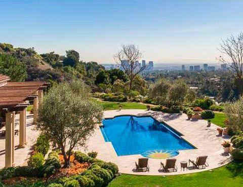 <p>Uno de los atractivos de la vivienda es la amplia piscina exterior, con vistas a los alrededores de Beverly Hills. También cuenta con una piscina cubierta, pista de tenis, gimnasio, biblioteca, bodega...&nbsp;</p>