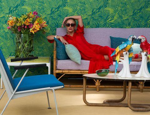 <p>El papel<i> Eden Roc</i>, de Designers Guild, en Usera Usera, 129 €/rollo, sirve de fondo a un sofá de bambú, en Old Madrid, 800 €. Los cojines son de Pez: verde agua, 150 €/cu, y gris, 225 €/cu. Butaca Le Corbusier, en Jon Urgoiti, c.p.v., como la mesa de centro, c.p.v.; con papagayos, 300 €/cu; El Ocho, y mesita años 50, en Schneider Colao, c.p.v., con florero y flores de Bourguignon. Ropa y accesorios, en Pez, y gafas, en Óptica Toscana.&nbsp;</p>