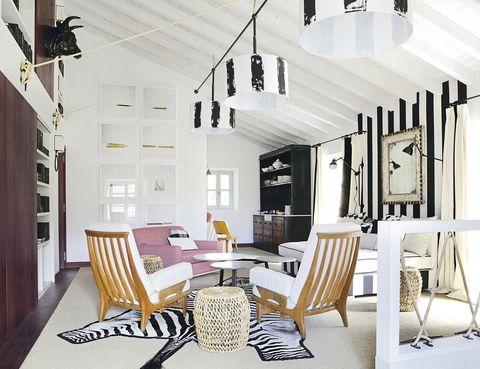 <p>La zona de estar tiene una potente personalidad. Se la dan las originales lámparas, diseñadas por el estudio de Marta de la Rica, y la cabeza de vaca de hierro que decora la pared, de Anmoder. Sillón rosa, de B&amp;B Collection, y mesa auxiliar de esparto, de Zara Home.</p>