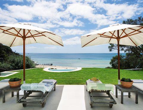 <p>Las tumbonas, en madera decapada y envejecida, y las sombrillas, de loneta cruda, componen un ambiente de marcado aire vacacional que invita al <i>dolce far niente</i> cerca de la piscina y con la mirada puesta en la playa privada.</p>