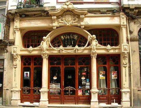 """<p>Nació a finales de 1921 llamándose Elite pero, solo un año después,&nbsp; pasó a llamarse Majestic un nombre, en palabras de su propietario, &quot;más acorde con las insignes personalidades que lo visitan&quot;.&nbsp;</p><p>Lo cierto es que el <a href=""""http://www.cafemajestic.com"""" target=""""_blank"""">Majestic Café</a>&nbsp;comenzó con buen pie y su inauguración convocó al top ten de las personalidades de la época, un acontecimiento social que estuvo a la misma altura que el de la famosa Libreria Lello e Irmão.</p><p>En el caso del Majestic fue João Queiroz el arquitecto encargado de firmar esta explosión modernista en la que no faltan rollizos angelitos, flores talladas en madera, vidrieras de colores, líneas curvas…&nbsp;</p><p>La estética art decó dejó poso y, junto a su elegancia, su emplazamiento –en la popular calle comercial de Santa Catarina– y su declaración como Patrimonio Cultural, el café es una visita obligada para los visitantes de Oporto. Por este local siempre abarrotado y con las mesas exageradamente juntas, han pasado escritores, políticos y artistas, incluso J. K. Rowling escribió aquí algunos capítulos de Harry Potter.</p>"""
