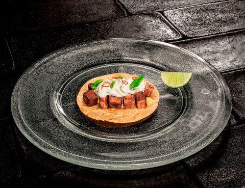 <p>Todos los aficionados a la buena comida han oído hablar -y muchos lo han probado- de <strong>Punto MX,</strong> el templo de la gastronomía mexicana en Madrid (General Pardiñas, 40), y el único azteca estrellado por Michelin en toda Europa. Pero el chef Roberto Ruiz, lejos de acomodarse, le ha dado otra vuelta de tuerca a la carta con la llegada de la primavera, y ha incluido un buen número de platos nuevos, muchos basados en productos y recetas indígenas ancestrales. Degustarlos -y hablamos con conocimiento de causa- es un verdadero lujo para los sentidos. El propio chef cultiva en su huerto las materias primas con las que elabora su nuevo <i>Tamal colado de rabo de toro con chipotle meco,</i> del que podríamos estar diciendo maravillas durante horas y aún así nos quedaríamos cortos. O su <i>Taco de Wagyu ahumado con chiles tatemados y tzatziki habanero</i> (en la imagen), para amantes de las emociones fuertes, o el delicioso <i>Guajolote con mole negro madurado por sesenta días…</i> Las novedades son espectaculares pero, si te acercas, no te vayas sin probar su receta más emblemática: el taco de <i>Tuétano a la brasa con salsa molcajeteada y majado de hierbas.</i> Te calará hasta los huesos, nunca mejor dicho. Los platos se sirven tanto en el restaurante como en el Mezcal Lab de arriba, donde puedes presentarte sin reserva. Eso sí, si no quieres esperar, acércate prontito. Merece -mucho- la pena. </p>