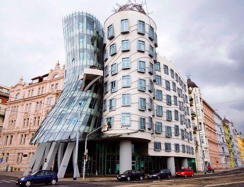 """<p><strong>Esperanza Gómez (secretaria de redacción).</strong> La Nationale Netherlanden, más conocida como La Dancing House (casa danzante) fue diseñada por Frank Gehry en 1996. Es un edificio deconstructivista, movimiento liderado por el propio Gehry, sus principios se basan en desechar las reglas de la arquitectura convencional y optar por el abandono de la línea recta, el gusto por ángulos no convencionales y olvidarse de la frase """"la forma sigue a la función"""". También conocida como Ginger y Fred, por su semejanza con una pareja de bailarines, se integra perfectamente con el resto de las edificaciones que conforman la ribera este del río Moldava.</p>"""