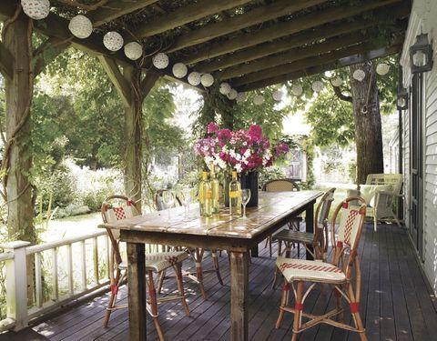 Unas sillas vintage rodean la mesa, de madera recuperada, en el comedor de esta casa de campo de Martha's Vineyard. Las guirnaldas son de Pearl River Mart y la vivienda es de Keith McNally, un restaurador afincado en Manhattan.