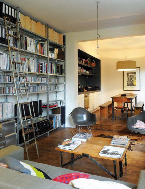 <p>El salón aúna piezas realizadas en metal, como la estantería modular y la escalera, que es reciclada, y muebles de madera.</p>