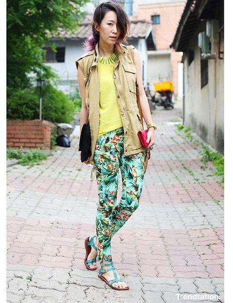 <p>Tomi combina los tonos tierra con los azules turquesa para crear un look muy llamativo, mezclando un toque sahariano del chaleco en color camel con el multicolor de los pantalones tropicales. Remata el outfit con un maxicollar dorado.</p>