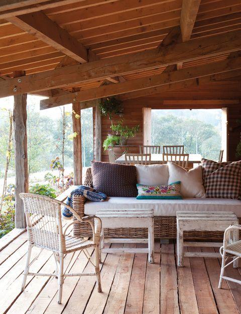 <p>La vida cambia de ritmo en el porche resguardado por vigas de pino. Un estar y un comedor permiten disfrutar del maravilloso paisaje. Sofá de ratán, de Isabel López-Quesada, sillas de enea de un brocante francés y banqueta de Hilary Batstone en madera reciclada.</p>