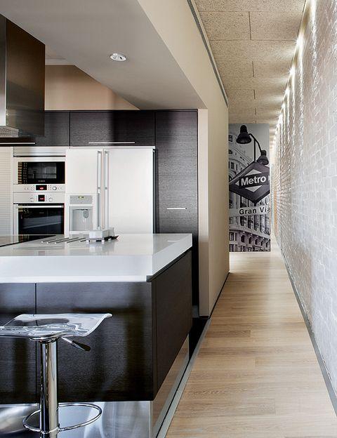 <p>La cocina: los muebles de <i>wengué</i>, de <strong>Doimo</strong> instalados por Dismuco, se rematan con una encimera de <strong> Corian</strong>. Los electrodomésticos son de <strong> Siemens</strong>; el frigorífico, de <strong>Gaggenau</strong>. Al fondo del pasillo, una puerta de aluminio con una fotografía de la mítica Gran Vía madrileña, impresa por <strong> Photosoul</strong>.</p>