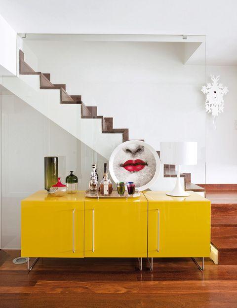 <p>Un toque de color en el mueble Plan, de Jasper Morrison para Cappellini, con delicadas piezas de Baccarat y de Venini, y un plato de Fornasetti. Lámpara, de Flos.</p>