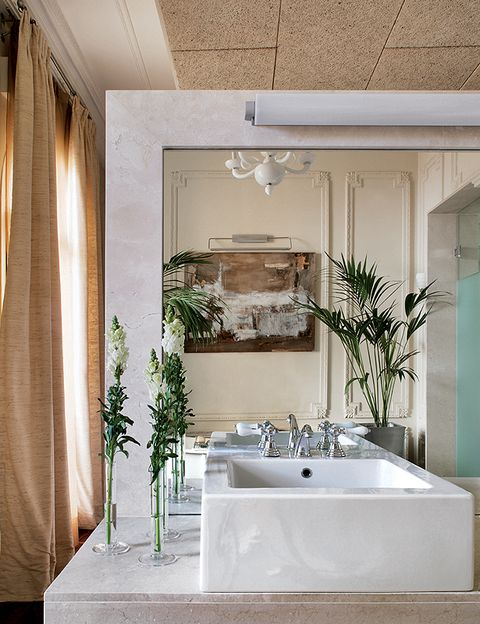 <p>En la zona del lavabo, el mármol es el protagonista. Las cortinas de seda son de <strong>Gancedo</strong>. Reflejada en el espejo, una obra gráfica de Baldomero Limón.</p>