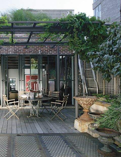 Un pequeño comedor compuesto por una mesa y unas sillas de hierro, también antiguas, permite comer en el exterior.