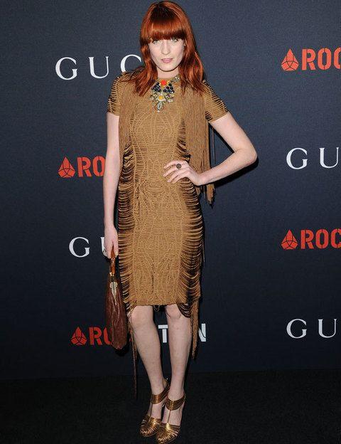 <p>Sería difícil describir el estilo de <strong>Florence Welch</strong> pues pasa por se vintage, seventies, romántico y lady. Nos gustó su ajustado vestido midi marrón con flecos que combinó con sandalias y bolso de aire retro.</p>