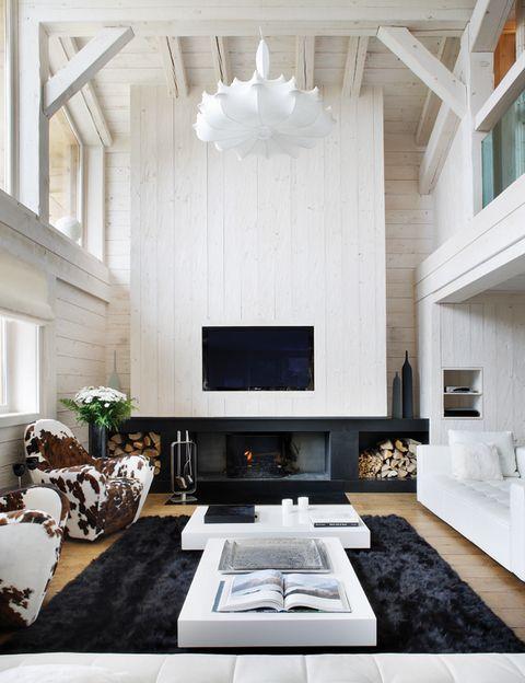 <p>La espectacular chimenea, que preside la zona de estar, combina granito negro de Zimbabwe y madera blanca en el gran panel que llega al techo y oculta el tiro. Sobre las leñeras, unas botellas altas talladas a mano de Dibbern. El cuadro lo firma David Martin.</p>