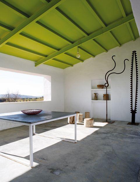 <p>El porche se amuebló con una mesa de zinc y acero, de Benjamín Cano, y unas magníficas esculturas en hierro, también del arquitecto.</p>
