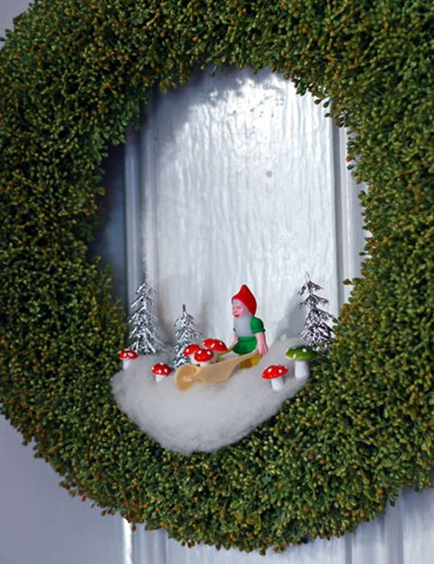 <p>Una buena idea es decorar la puerta de casa con una bonita corona. Y, si además le añades un poco de nieve, unos árboles, unas setas y un gnomo... ¡queda perfecto!</p>