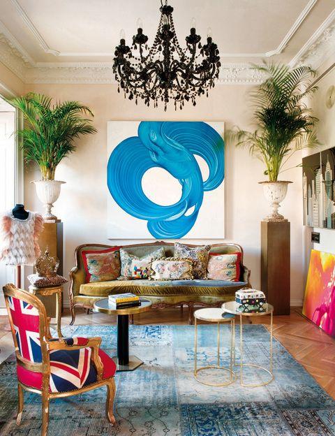 <p>La obra de David Palmer convive con un sofá estilo Luis XVI, tapizado por Bea con distintos trozos de tela de MCH. Dos peanas sostienen copas francesas de Anmoder, al igual que las mesitas. La alfombra es de Carpet Reloaded.</p>