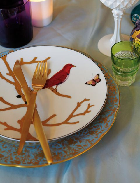 <p>Los platos de porcelana: el de arriba, de postre, está decorado con motivos de pájaros, y el de abajo, azul y oro, es de estilo decimonónico, de Bernardaud. Los cubiertos, de acero dorado mate, en Zara Home. Vaso violeta, en Merci, y vaso de chupito verde, en Cristalerías de Saint Louis.</p>