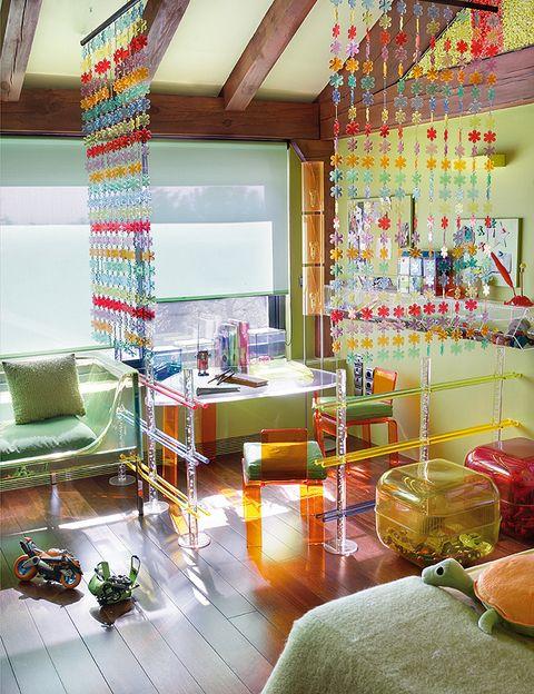 <p>En la habitación del más pequeño de los niños, los muebles y tejidos en colores ácidos rinden culto al caramelo; los huecos entre vigas se rellenaron de muñecos, chuches y juguetes. Para amueblarla, se han elegido piezas transparentes en colores divertidos, como la mesita y las sillas, de <strong>Baus Design</strong>, y el sofá <i>Phanton</i>, de <strong> Driade-Store</strong>.</p>