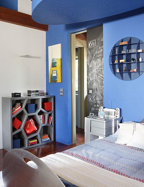 <p>En el dormitorio del mediano reina el color azul cielo, su favorito. La zona está presidida por la cama, diseño de la propietaria, con luces y señalizaciones incorporadas. Sobre ella, una manta de <strong>Becara</strong>. La estantería gris, <i>Opus Incertum</i>, es de <strong>Casamanía</strong>, y el cuadro es de Teresa Rodríguez Ortiz.</p>