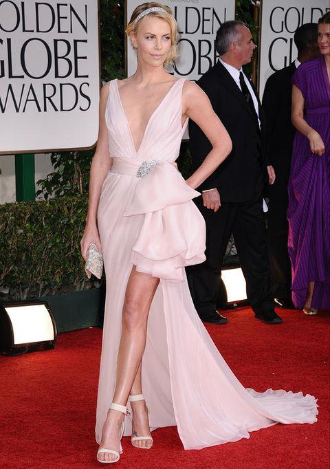 <p>Una espectacular <strong>Charlize Theron</strong> hizo su aparición con este <strong>Dior Couture </strong>color rosa maquillaje con falda asimétrica con detalle joya en el cinturón. Su recogido con ondas y adornado con una banda joya a juego con su clutch, y las sandalias al tobillo completaban su sofisticado look y uno de nuestros favoritos.</p>