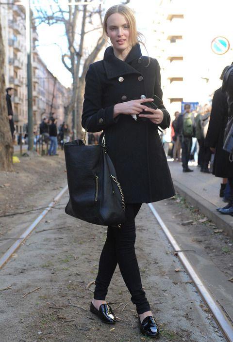 <p>Esta modelo luce un look total black (móvil incluido) con un maxi bolso con detalles dorados y zapatos de charol.</p>