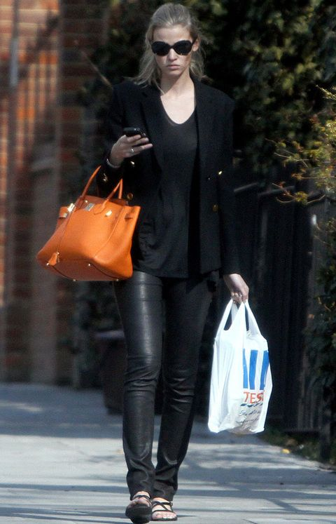 <p>¿La mejor forma de romper un<i> 'total black'</i>? Con un colorido bolso. Ficha el look de calle de la modelo Lara Stone con pantalones de cuero negros y bolso de mano naranja <strong>Birkin de Hermès.&nbsp;</strong></p>