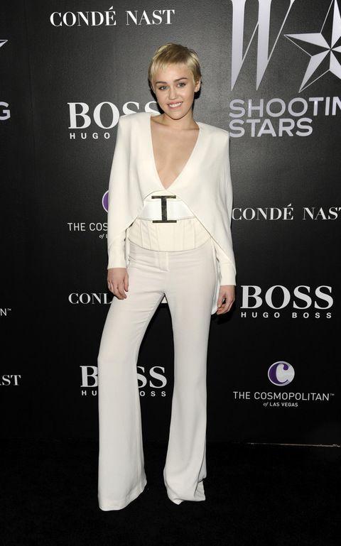 <p>Miley también se viste de blanco pero con un traje capa de escote en unve muy elegante.</p>