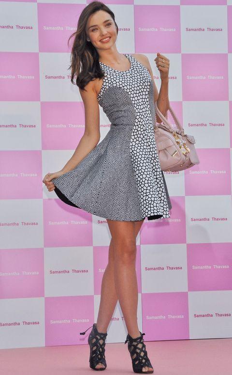 <p>Trendy, elegante y muy femenina. Así luce <strong>Miranda Kerr</strong> con este vestido con dos estampados en gris y negro. Muy acertados también su bolso de mano en color maquillaje y las sandalias negras.&nbsp;</p>