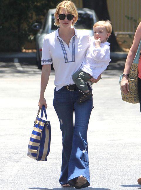 <p>Nada favorecedores los pantalones campana de<strong> January Jones.</strong> De su look nos quedamos con el bolso a rayas azul y nude.</p>