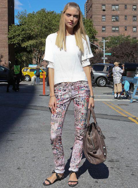 <p>Esta modelo combina perfectamente sus pantalones con print sicodélico multicolor con una sencilla camiseta blanca, sandalias planas y maxibolso.</p>