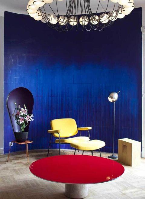 <p>En el salón, la gran tela azul que viste la pared es un trabajo de Latifa Echakhch; delante destaca un gran jarrón negro de los Bouroullec.</p>