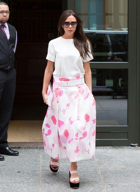 <p>¿Qué sería de nosotras cada verano sin un básico como una camiseta blanca? <strong>Victoria Beckham</strong> luce la suya en un look a la última con falda midi de flores y plataformas.</p>