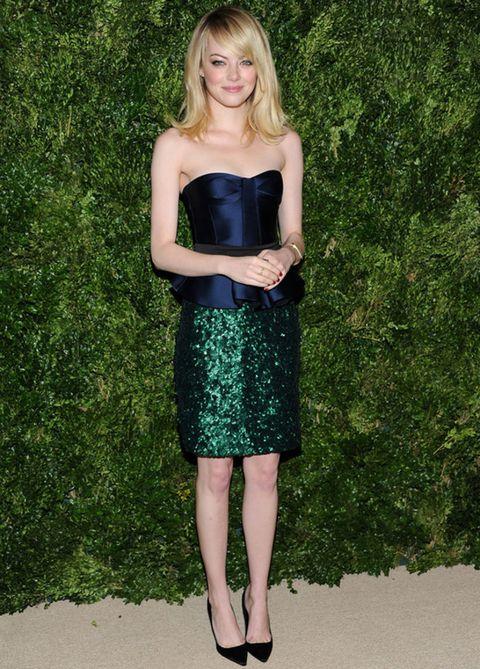 <p><strong>Emma Stone</strong> deja las lentejuelas sólo para su falda en verde esmeralda que combina con un top de satén azul marino palabra de honor entallado con cinturón negro para darle un efecto peplum, todo de <strong>Burberry Prorsum Spring 2013</strong>.</p>