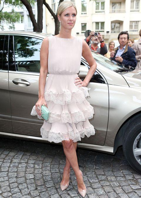 <p><strong>Nicky Hilton</strong> con un look muy romántico en el desfile de Valentino con un vestido plisado y con volante de encaje en blanco roto con salones nude y clutch joya turquesa.</p>