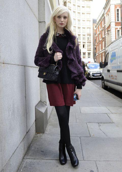 <p>Falda color burdeos, camiseta de corte peplum con cuello de bebé de pedrería, abrigo de pelo, bolso 2.55 de Chanel y botines.</p>