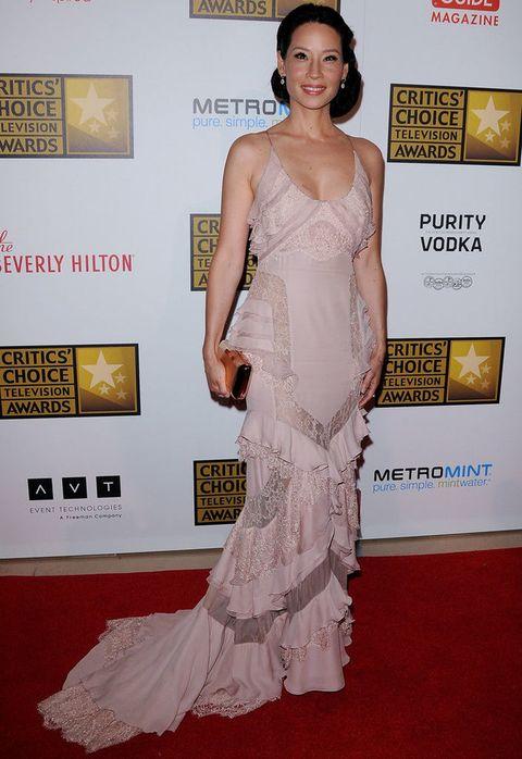<p>Muy elegante, la actriz <strong>Lucy Liu</strong> apostó por ir de largo con este vestido rosa palo con detalles de encaje y un clutch naranja.</p>