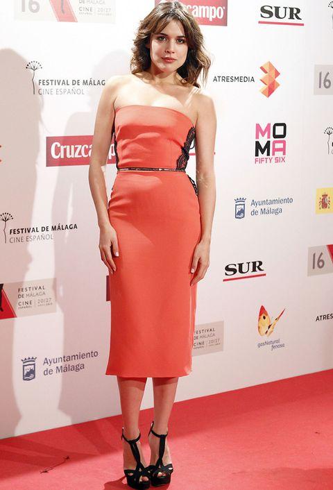 <p><strong>Adriana Ugarte</strong> acertó con su vestido midi palabra de honor en coral con detalle lateral de encaje, cinturón XS y sandalias en negro.&nbsp;</p>