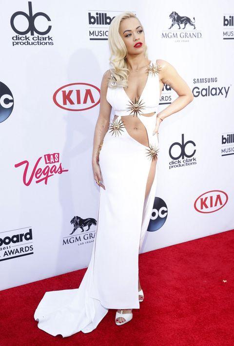 <p>Siguiendo la tónica de la noche,<strong> Rita Ora</strong> apostó por ir de blanco con un sensual vestido con detalles en dorado, aberturas 'cut out' y falda abierta hasta la cadera de <strong>Fausto Puglisi</strong> y sandalias de <strong>Giuseppe Zanotti</strong>.</p>
