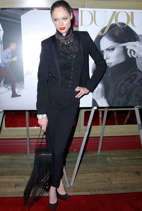 <p>La modelo <strong>Coco Rocha</strong> se apunta al tuxedo en este 'total black' que combina con collar joya y bolso de mano con flecos XL.</p>
