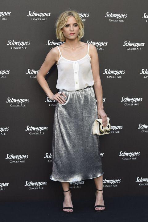 <p><strong>Ana Fernández</strong> combinó un top de tirantes blanco con una falda midi metalizada, sandalias negras y un original bolso.</p>