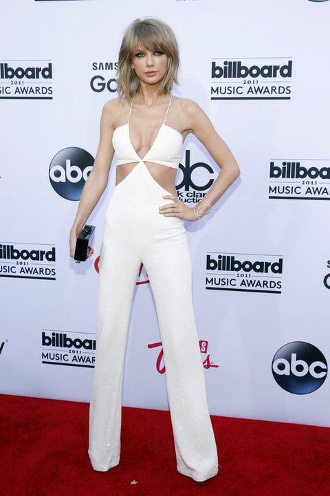 <p><strong>Taylor Swift</strong> dejó los vestidos largos a un lado y eligió este mono blanco de tirantes con aberturas en la cintura de <strong>Balmain Primavera 2015</strong>, combinado con un clutch negro de <strong>Edie Parker</strong>.</p>