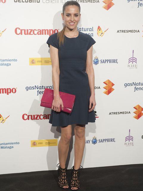 <p><strong>Ana Fernández</strong> combinó un minivestido lady en gris con sandalias jaula negras y una cartera XL en rosa fucsia.</p>