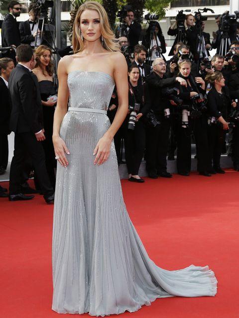 <p>Sin palabras nos dejó la modelo <strong>Rosie Huntington-Whiteley</strong> sobre la alfombra roja de Cannes con este vestido de <strong>Gucci Première</strong>. Un diseño palabra de honor en seda gris con detalles de strass en cascada y cintura enmarcada combinado con joyas de <strong>Grisogono</strong>. Su melena natural con ondas también fue todo un acierto.</p>