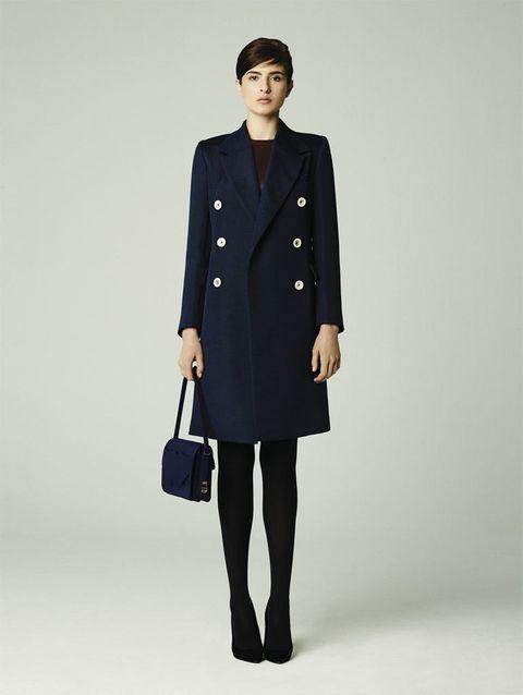 <p>Abrigo con aire militar con botonadura en color marino y bolso de mano en la misma tonalidad.</p>