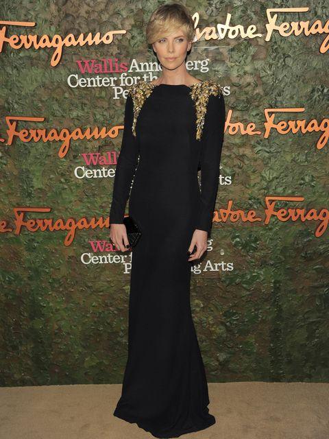 <p><strong>Charlize Theron</strong> fue una de las invitadas más elegantes con este espectacular vestido negro largo con apliques dorados en los hombros de <strong>Alexander McQueen Pre Fall 2013</strong>&nbsp;combinado con un mini clutch también en negro de <strong>Ferragamo</strong>.&nbsp;</p>